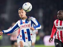 Luciano Slagveer (l.) passeert Jetro Willems (r.) met een kopbal.(22-01-2017)