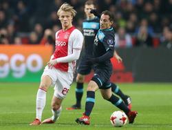 Andrés Guardado (r.) geeft in de eerste minuten van de wedstrijd tussen Ajax en PSV met zijn knie een tikje op het bovenbeen van Kasper Dolberg (l.). (18-12-2016)