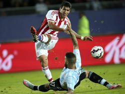 Marcos Cáceres intenta disparar ante la presión de Nicolás Otamendi. (Foto: Imago)