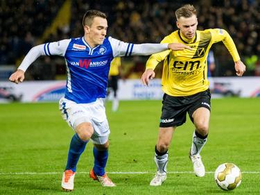 Daan Disveld (l.) gebruikt zijn arm om in ieder geval in de buurt te komen van de bal, die in het bezit is van Danny Verbeek. (20-11-2015)