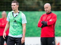 Nieuwbakken Ajax-trainer Peter Bosz (r.) kijkt van een afstand toe hoe onder anderen Nick Viergever (l.) het doet op de eerste training. (29-06-2016)