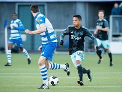 Justin Kluivert dribbelt namens Ajax op met de bal. PEC Zwolle-verdediger Ted van de Pavert loopt met hem mee (15-01-2017)