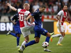 Davy Klaassen (l.) doet er alles aan om Stefanos Athanasiadis (r.) van de bal te zetten. (26-07-2016)