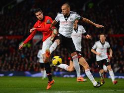 John Heitinga (r.) en Robin van Persie (l.) strijden om de bal tijdens Manchester United - Fulham. (9-2-2014)