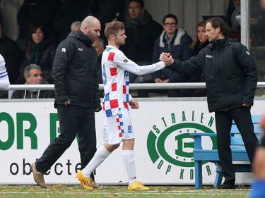 Dennis Kaars (m.) krijgt een hand van assistent-trainer Olaf Lindenbergh (r.) tijdens het competitieduel De Dijk - Jong FC Den Bosch (13-11-2016).