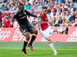 Ajax-debutant Hakim Ziyech (r.) vecht een duel uit met Marvelous Nakamba (l.) tijdens het competitieduel Ajax - Vitesse (11-09-2016).