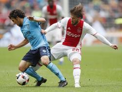 Lasse Schöne (r.) tikt de bal bij de voeten van Yassin Ayoub (l.) weg tijdens Ajax - FC Utrecht. (02-10-2016)
