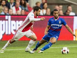 Amin Younes (l.) probeert tijdens een competitieduel van Ajax zijn tegenstander Pele van Anholt (r.) van Willem II uit te spelen. (20-08-2016)