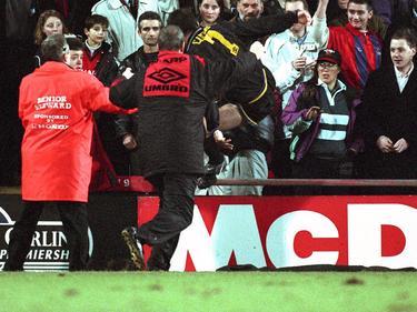 1995 springt Manchester Uniteds Éric Cantona (M.) über die Absperrung und tritt einen Fan um