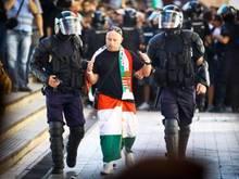Ein ungarischer Fußballfan wird von rumänischen Polizisten abgeführt