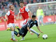 Die Berliner Martin Dausch (l) und Fabian Schönheim (r) nehmen den Münchner Bobby Wood in die Zange. Foto: Oliver Mehlis