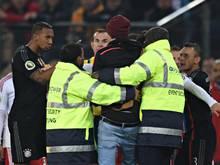 Der Platzstürmer nach seiner Attacke von Jerome Boateng zurechtgewiesen
