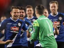 Außer sich vor Freude bestürmt die Mannschaft von Arminia Bielefeld ihren Torwart Alexander Schwolow
