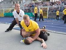 Sicherheitskräfte überwältigen nach Spielende einen Anhänger des FC Carl Zeiss Jena