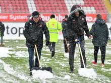 Mitarbeiter räumen das Spielfeld in Kaiserslautern vom Schnee