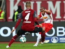 Nürnbergs Ewerton (l.) blockt im Spiel gegen Jahn Regensburg einen Ball von Jann George