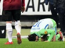 """Wolfsburgs Yunus Malli küsst den Rasen im Stadion von Hannover 96: """"Ich kann mich nicht erinnern, je auf einem so schlechten Platz gespielt zu haben"""", sagte Torschütze."""