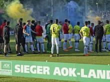Die Cottbusser beobachten nach dem Pokalsieg die Pyroaktionen der Babelsberger Fans.