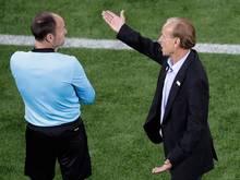 Nigerias Trainer Gernot Rohr (r) diskutiert beim Spiel gegen Kroatien mit dem vierten Schiedsrichter.