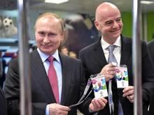 Russlands Präsident Wladimir Putin (l) und FIFA-Präsident Gianni Infantino zeigen beim Betreten eines Stadions ihre Fan-ID