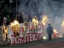 Vermummte Fans verbrennen während des Derbys ein Banner vor den Zuschauertribünen
