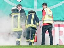 Feuerwehrleute löschen brennende Bengalos, die von Mainzer Fans aufs Spielfeld geworfen wurden
