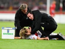 Borna Sosa vom VfB Stuttgart wird von den Mannschaftsärzten behandelt