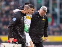 Gladbachs Laszlo Benes (M) muss verletzt vom Platz und wird dabei von zwei Betreuen gestützt