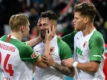 Augsburgs Fredrik Jensen (l) und Florian Niederlechner (r) freuen sich mit Torschütze Marco Richter über den Führungstreffer
