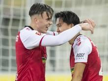 Woo-yeong Jeong (r) und Ermedin Demirovic feiern ein Tor für den SC Freiburg