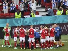 Dänemarks Spieler schirmen ihren Teamkollegen Christian Eriksen während der lebensrettenden Maßnahmen ab