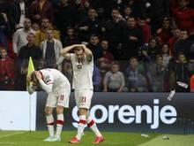 Polens Spieler schützen sich vor den Flaschenwürfen durch albanische Fans
