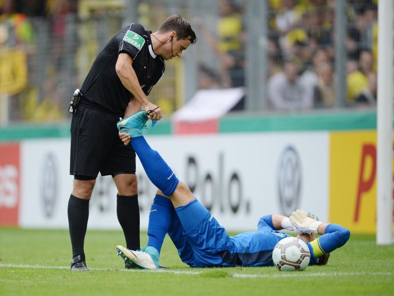 Schiedsrichter Christian Dietz hilft Torwart Dennis Klose, der mit einem Krampf auf dem Boden liegt