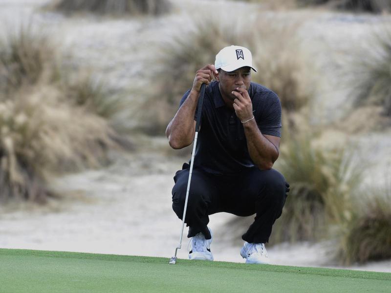 Tiger Woods schaut sich die Puttlinie ganz genau an. Foto: Dante Carrer