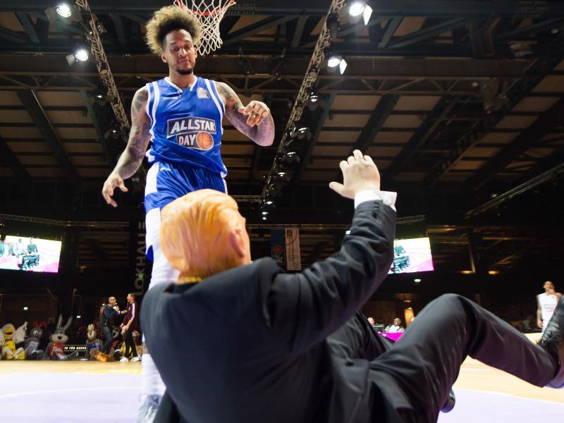 Julian Gamble von den Telekom Baskets Bonn dunkt über einen als Donald Trump kostümierten Mann