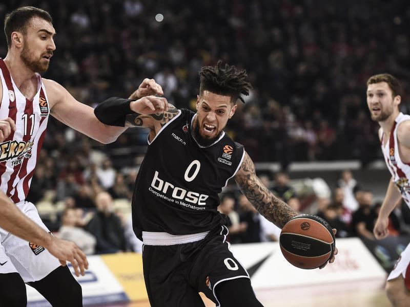 Bambergs Daniel Hackett (M) setzt sich gegen Kim Tillie (l) von Olympiakos Piräus durch