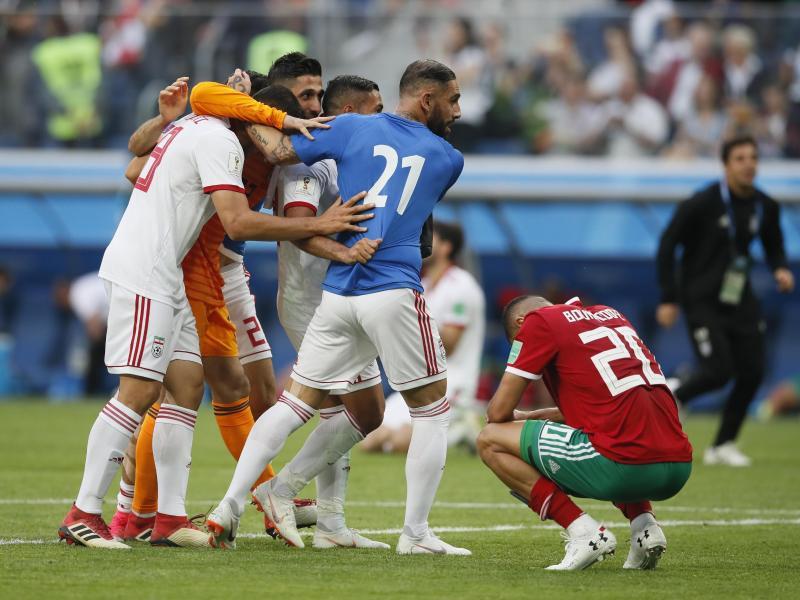 Der Marokkaner Aziz Bouhaddouz (r.) hockt nach seinem Eigentor auf dem Rasen, während die Spieler des Iran den Sieg bejubeln