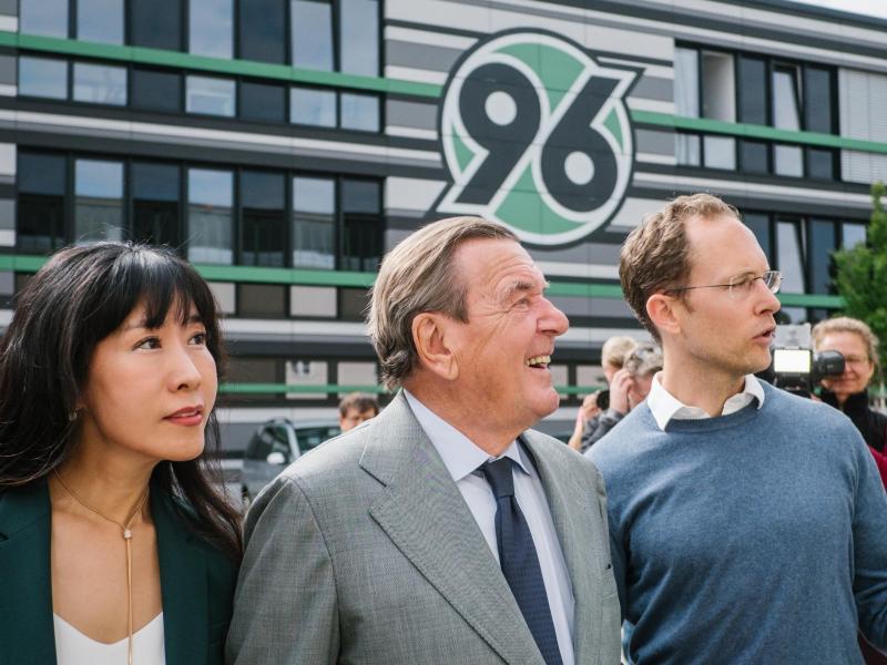 Altkanzler Gerhard Schröder (M.), auch Aufsichtsratsvorsitzender von Hannover 96, besucht mit seiner Ehefrau (l.) die Nachwuchsakademie des Vereins.
