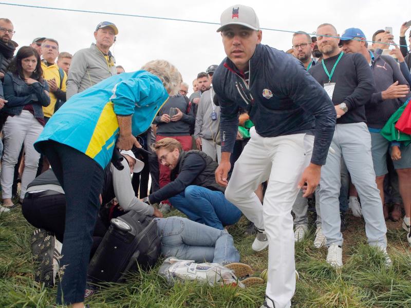 Brooks Koepka (M.) vom Team USA steht neben der Zuschauerin, die von seinem Golfball getroffen wurde