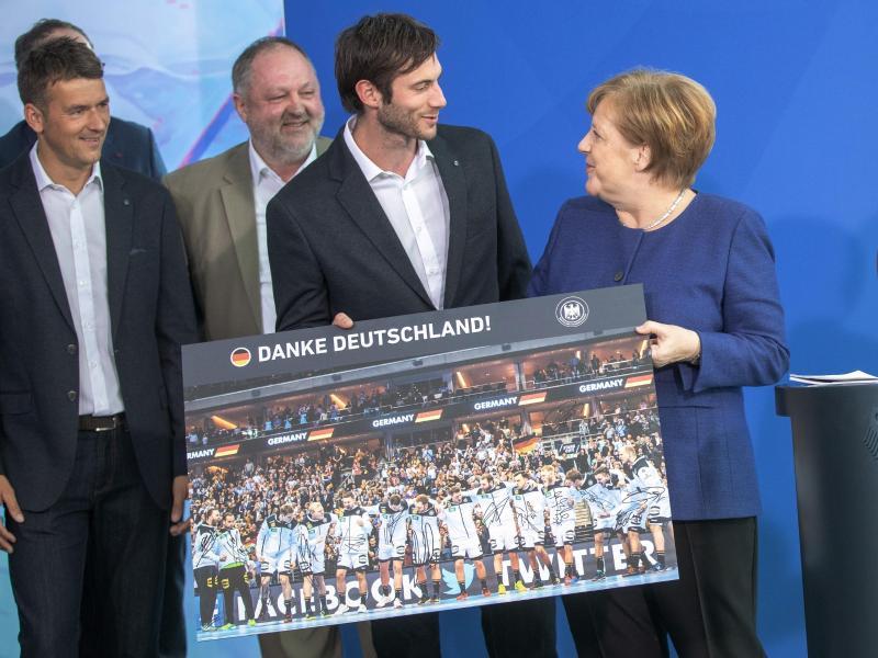 Angela Merkel (r.) bekam ein Bilder der deutschen Nationalmannschaft überreicht