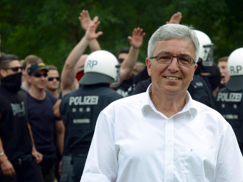 Der rheinland-pfälzische Innenminister Roger Lewentz und Polizeibeamte im Hintergrund