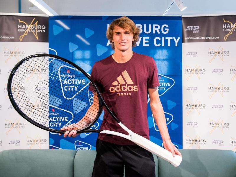 Alexander Zverev posiert in Hamburg während einer Pressekonferenz mit einem überdimensionalen Tennisschläger