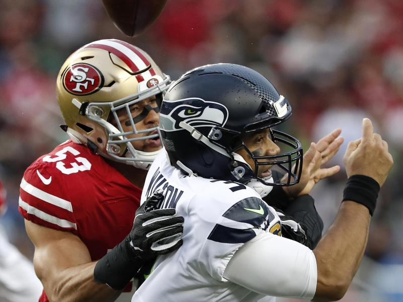 Mark Nzeocha (l) von den San Francisco 49ers in Aktion gegen Seahawks-Quarterback Russell Wilson