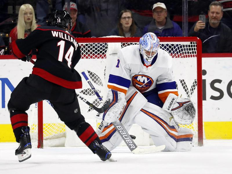 Justin Williams (l) von den Carolina Hurricanes in Aktion gegen Goalie Thomas Greiss von den New York Islanders