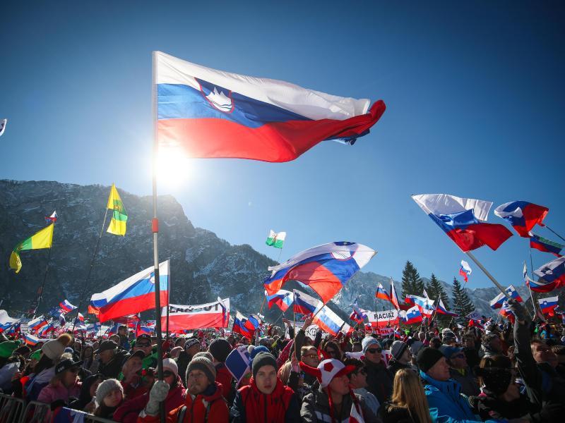 Fans schwenken die slowenische Flagge - die Skiflug-WM kann trotz des Coronavirus stattfinden