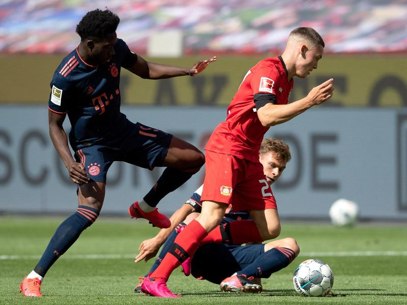 Leverkusens Florian Wirtz (r) setzt sich gegen Alphonso Davies vom FC Bayern durch. Foto: Matthias Hangst/Getty Images Europe/Pool/dpa