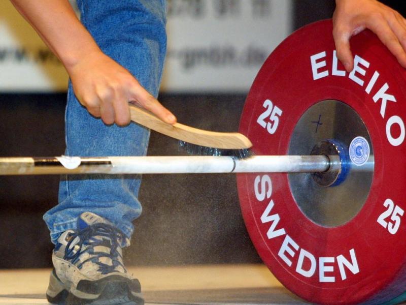 Ein Mann reinigt eine Hantel mit einer Bürste. - Die Internationale Gewichtheber-Föderation macht negativ von sich reden. Foto: Patrick Seeger/dpa