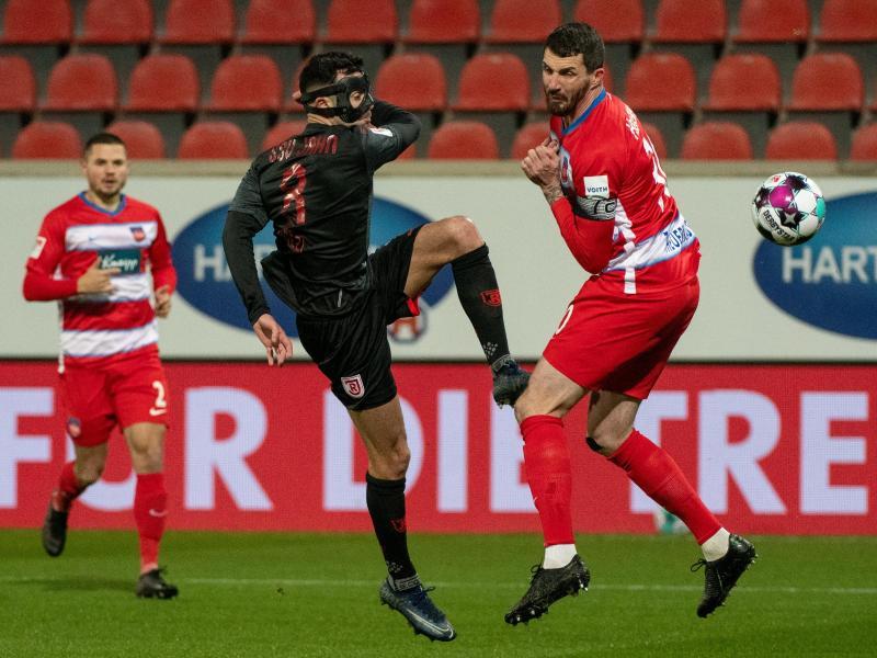 Heidenheims Norman Theuerkauf (r) und Regensburgs Albion Vrenezi teilten sich mit ihren Teams die Punkte