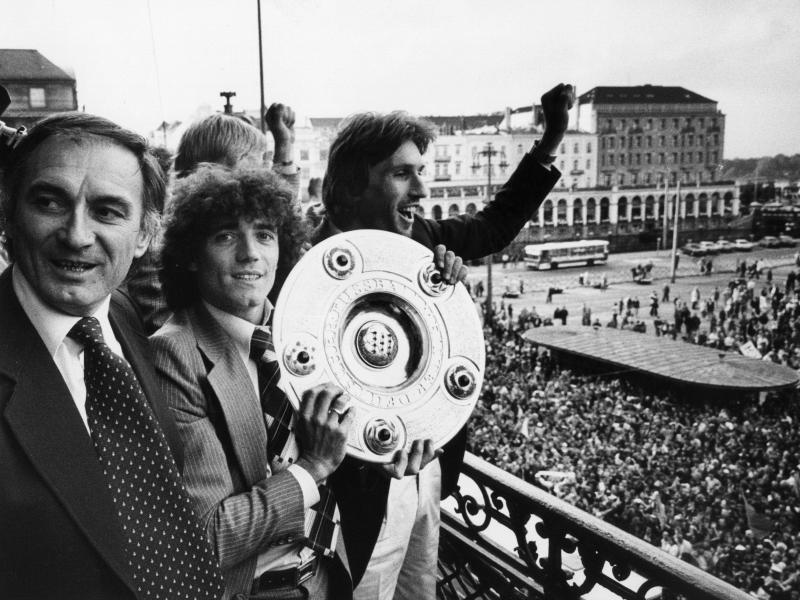 Kevin Keegan (M) feiert mit Meisterschale in Händen zwischen HSV-Trainer Branco Zebec (l) und Abwehrspieler Manfred Kaltz den Erfolg