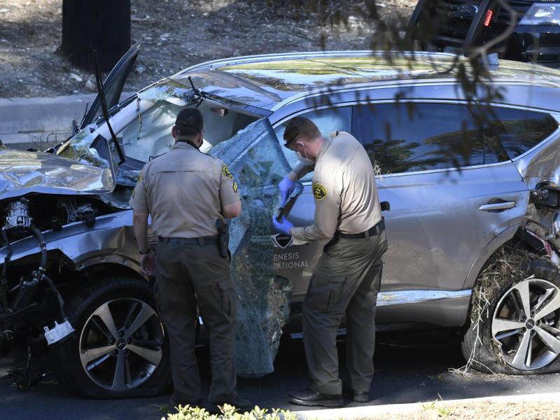 Polizisten inspizieren das beschädigte Fahrzeug von Tiger Woods nach dem Unfall